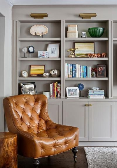 Cognac leather tufted corner reading chair is positioned on caster legs in front of built in styled gray bookshelves located above gray shaker TV cabinets fitted with brass hexagon knobs lit by brass picture lights.