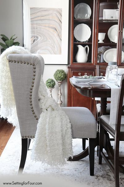 See my dining room update with these gorgeous linen wing back chairs with nail head trim, white dinnerware made in Portugal, terrariums and gray accents!