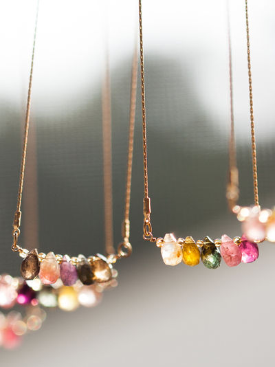Delicate satin gold plated snake chain featuring multi-colored teardrop shaped watermelon tourmaline stones. Adjustable lobster clasp closure. American made.