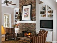 Stacked Stone Fireplace in the Living Room Combined Chairs, LCD TV, and White Cabinet