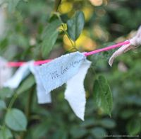guests write messages to baby and tie them to garland