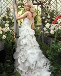 """Here, a strapless ivory gown turns heads with its voluminous train of blossoming organza. Vera Wang """"Ghilian"""" gown."""