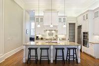 #Kitchen of the Day: A classic white kitchen with extra-high ceilings, over-cabinet lighting, oak hardwood floors, and a large island. (Kitchen-Design-Ideas.org)