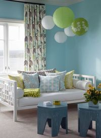Fun girl's room with bright blue walls paint color, peacock blue octagon stools tables, white West Elm overlapping squares daybed, white & green paper lanterns and green blue brown floral window panels curtains.
