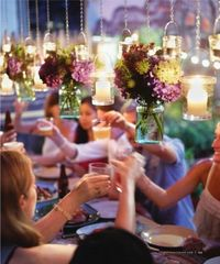 I love this idea of instead of centerpieces that block people's view, these candles and vases of flowers are suspended above the table