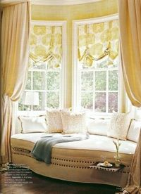 A deep bow window with soft roman shades and drapery panels to create the feeling of a little enclave. The sofa has little pull-out trays camouflaged by nailheads. Kitschy?