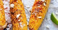 Mexican Grilled Corn (Elote) - Corn on the cob is grilled, brushed with mayo, and topped with chile powder, goat cheese, and lime.