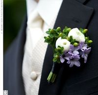 Boutonniere, composed of green hypericum berries, white ranunculus, and purple lilac blossoms.