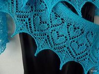 Irmelie is a simple and elegant lace shawl, with a crescent shape that makes it drape well over the shoulders. It features a beautiful lace edge with heart shaped motifs, and a simple stockinette stitch body. It is worked from the outer edge, and is shape...