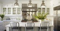gorgeous kitchen design with glass-front cabinets, creamy white kitchen cabinets, white carrara marble counter tops, subway tiles backsplash, industrial yoke island pendants, 1006 Navy counter stools and stainless steel appliances.