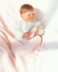 This baby afghan knitting pattern uses circular needles to create a cozy cover for baby. The extra-large blanket will last into the toddler years.