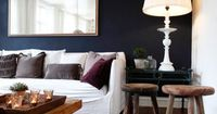 This room is wonderful: Dark, bold wall highlighted with a simple white slip covered couch, a bright lamp with great lines, and a reflecting light/space mirror. Rustic wood accents and a variety of fabric muted color pillows and of course a little greener...