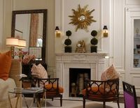 Paneling, mantelpiece, orange, gilt clock and mirror, topiaries.