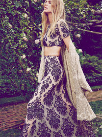 Illusion crop top maxi set with an allover embroidered brocade lace on mesh. Top features and elastic waistband and nude lining. Skirt has a half slip with a hidden side zip.