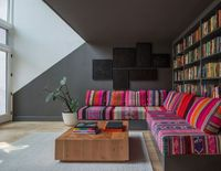 In the basement lounge area under the stairs, Lee had a giant sofa is upholstered in 18 Peruvian blankets that JHID collected over several months. The paintings are by Heather Watkins, a Portland artist. The coffee table is custom design in solid fir, whi...