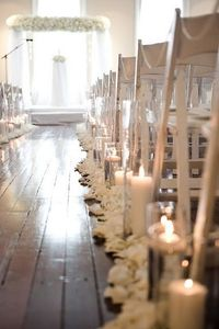 Absolutely Elegant!! Simple white rose petal on the edge of the aisle, with candle light and a gorgeous floral and drape alter.