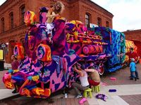 While some crafters enjoy creating koozies for just about anything, famous yarn-bomber Olek has taken on the ambitious task of covering a four-car locomotive wi