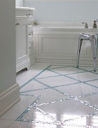 Beautiful bathroom features a traditional white sink vanity accented with nickel cabinet pulls alongside a wainscoting paneled tub beside a polished aluminum stool atop white diamond tiled floors accentuated by turquoise mosaic trim.