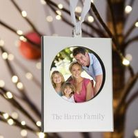 Silver-toned frame ornament. Frame unsnaps opens to insert picture and is secured with a delicate ribbon. Made of tarnish resistant steel.
