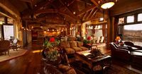 Spacious Montana Great Room with high arched wood beams has comfortable leather and fabric upholstered furniture.