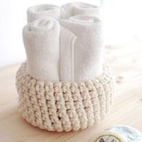 Crochet your own bowls from some rope bought at the hardware store + pattern.