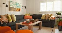contemporary family room. Charcoal sectional, paneling, sconces, tangerine accents | Bonesteel Trout Hall