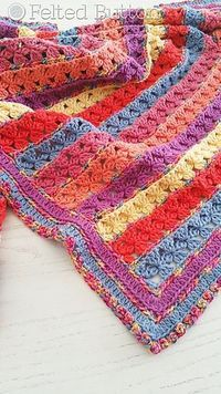Little Rows of Posies separated by a shimmery and colorful variegated yarn makes for a sweet and happy blanket. Bust your stash or use the colors shown in the sample.