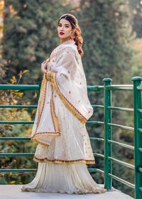 This stunning formal wedding wear is accompanied by an organza gown which is embellished with tilla, thread, pearls and Dapka Zardozi work. A gold net heavy dupatta and a plain gold tissue lehnga with crushed chiffon on hem truly raises the vibe, entirely...