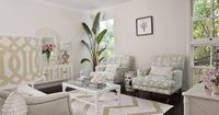 Seafoam green and beige living room design with light tan walls paint color, white & beige zigzag chevron rug, glossy white hollywood Regency pineapple lamp with Kelly Wearstler imperial trellis lampshade, gray nailhead trim sofa, seafoam green chairs...