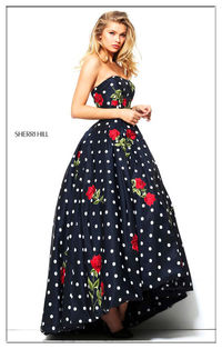 Fabulous Sherri Hill prom dress 50945 is made in a polka dot printed fabric and embellished with elegant floral appliques. The top features a straight across strap less style and the bottom showcases a full A-line skirt with a T length that will let you s...