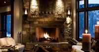 Love the stone fireplace and cozy furniture arrangement. The ceiling beams look modern and fresh too.