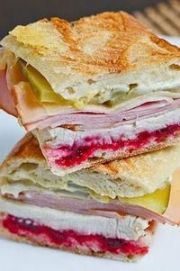 A tasty Thanksgiving style Cuban sandwich with roasted turkey, smoked ham, swiss cheese, pickles and cranberry sauce.