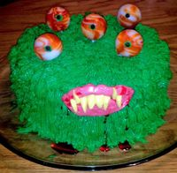 Monster Cake. Fur: green frosting piped using grass tip. Eyes: suckers with mini choco chips for the iris. Mouth & teeth: sculpted taffy. Blood: strawberry syrup.