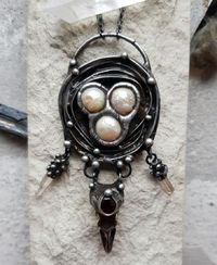 This is a pendant about a nest in which the past / ancestors (raven skull) guard the future generation (bird eggs from pearls). $78.00
