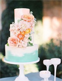 Mint and peach wedding cake with flowers.