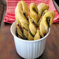 Twisted bread sticks with pesto, sun-dried tomatoes and Parmesan cheese. Perfect pairing for soup and salad.