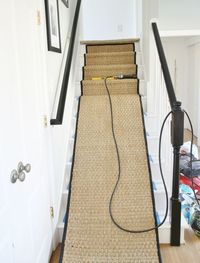 Disgusted with your ugly carpeted stairs? Transform the look of your home with this white painted staircase makeover with seagrass stair runner tutorial.
