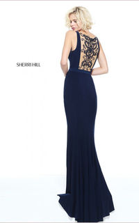 Show off your gorgeous figure in this glamorous Sherri Hill prom dress style 51096. This jersey material dress features a sexy plunging illusion neckline as a solid belt cinches in your waist. Crystals embellishments sparkle along the sheer back panel, ad...