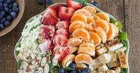 A healthy and incredibly simple spinach salad topped with chicken breast, strawberries, blueberries, toasted almonds, feta cheese, clementines, a squeeze of lem