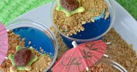 Tropical turtles bask on a sandy graham cracker beach in these adorable and fun blue raspberry Jello cups.