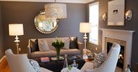 Chic gray living room design with gray purple wlls paint color, sunburst mirror, gray sofa with nailhead trim, ivory chairs, gray purple tufted rectangular ottoman, hammered metal sconces, mercury glass vases, Windsor Smith pelagos fabric pillows, Arterio...