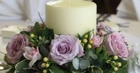mauve flower arrangements | Table centre of chunky candle with wreath of flowers around.